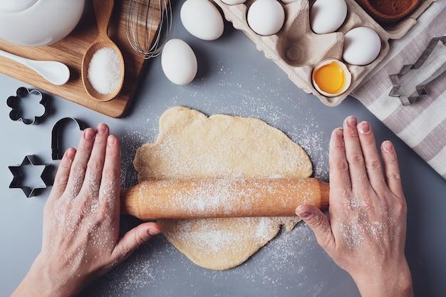 A garota desenrola a massa com um rolo de madeira para fazer biscoitos ou biscoitos. composição plana com utensílios e ingredientes de cozinha, copie o espaço. conceito de panificação para o feriado.