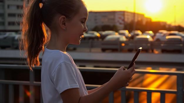 A garota digita no smartphone e posa para uma selfie ao pôr do sol