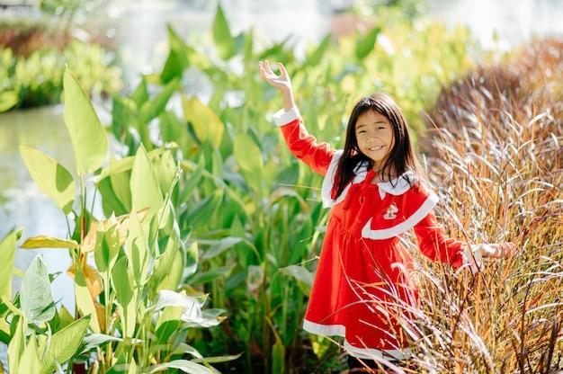 A garota do vestido sandy sorriu, riu e se divertiu. entre os arbustos