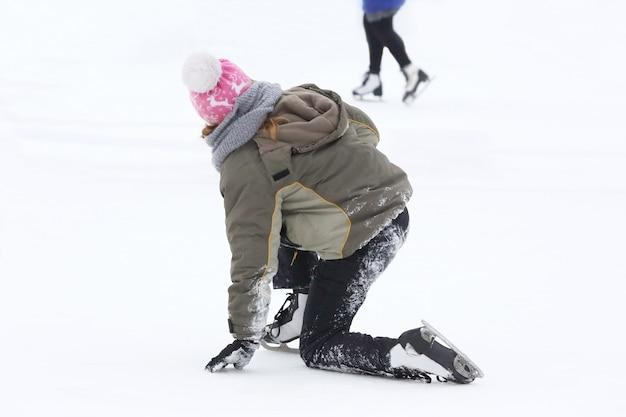 A garota dos patins se levanta após uma queda na pista de gelo