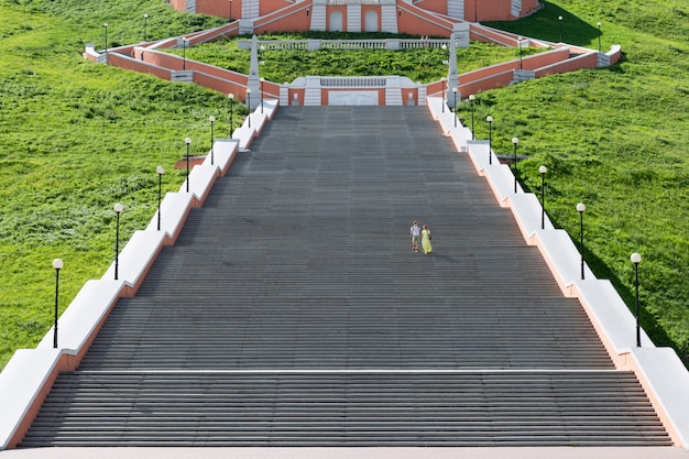 A garota e o cara descem as escadas enormes.