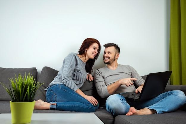 A garota e o cara se divertem para o laptop
