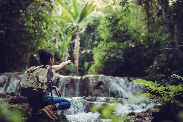 A garota é refrescante em riachos na floresta tropical.