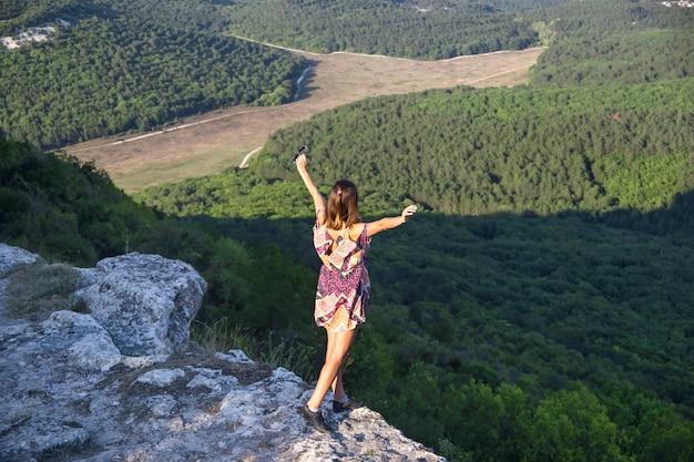 A garota é um viajante de pé no topo de uma montanha e um penhasco