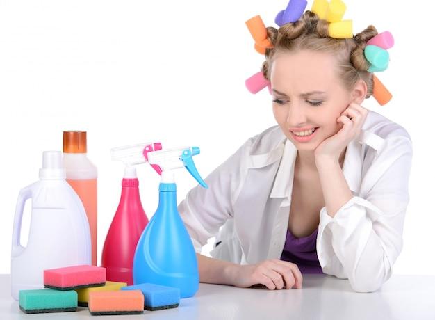 A garota em rolos olha para os dispositivos de limpeza.