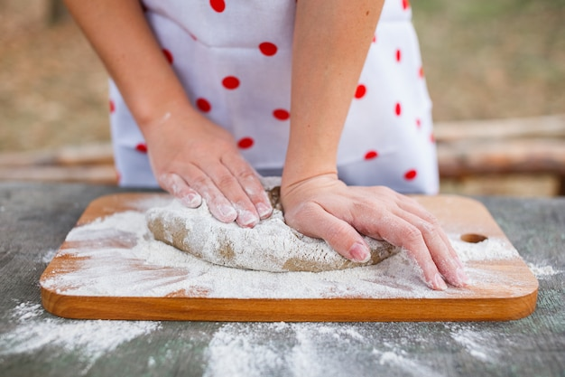 A garota em um avental branco prepara a massa em uma placa de corte