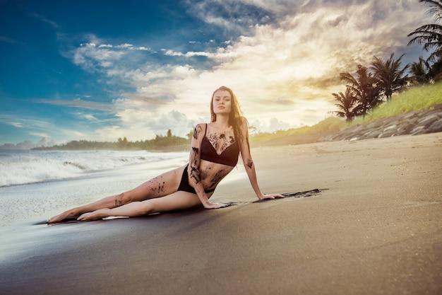 A garota em um maiô coberto de areia preta está deitada na praia no pôr do sol e no oceano