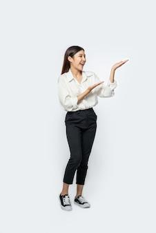 A garota em uma camisa branca e o sinal de mão aberta na lateral
