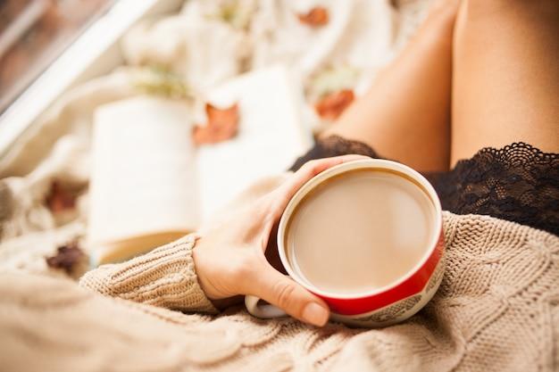 A garota em uma camisola de malha aconchegante beber café de uma caneca vermelha