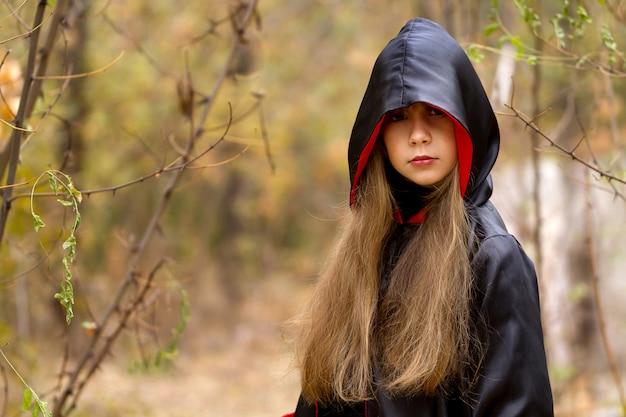 A garota em uma capa vermelha e preta na floresta