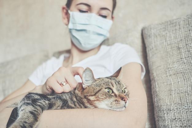 A garota em uma máscara médica está em auto-isolamento em casa e está descansando com um gato no sofá.
