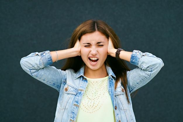 A garota, em voz alta, fechou os ouvidos com as mãos