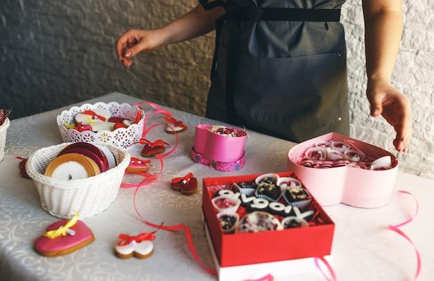 A garota embala os bolos em caixas de presente coloridas.