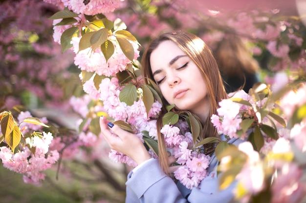 A garota encontra-se em flores de sakura. uma linda garota dorme em um jardim de flores