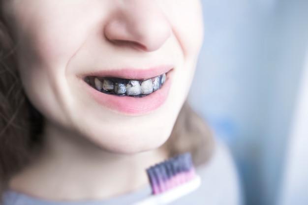 A garota escova os dentes com carvão de pasta preta