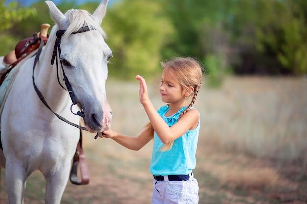 A garota está acariciando um pônei branco. a criança se comunica com o cavalo