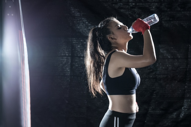 A garota está bebendo água enquanto descansava de treinamento de boxe no ginásio.