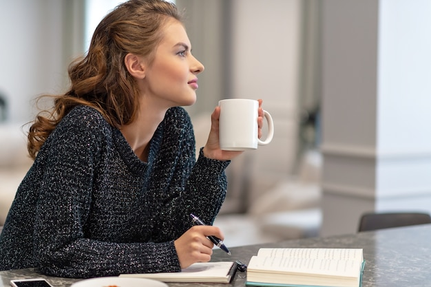 A garota está em casa mulher sozinha em seu quarto. ela está sentada na mesa e escrevendo algo em seu caderno usando o lápis