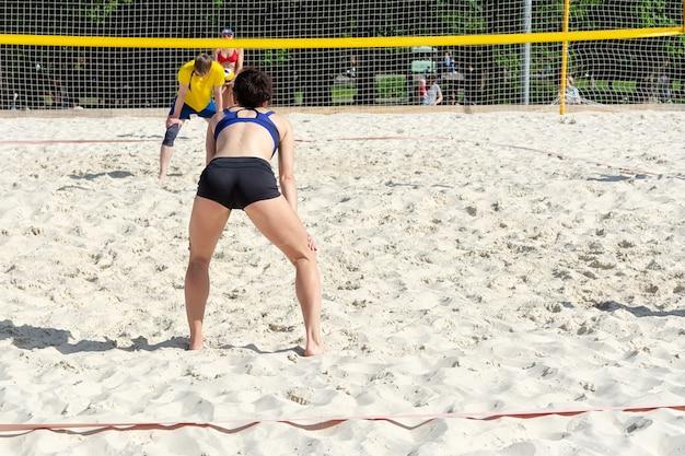 A garota está esperando a bola na quadra de vôlei de praia da equipe adversária.