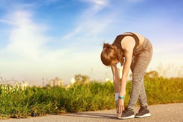 A garota está esticando o corpo antes de correr de manhã.