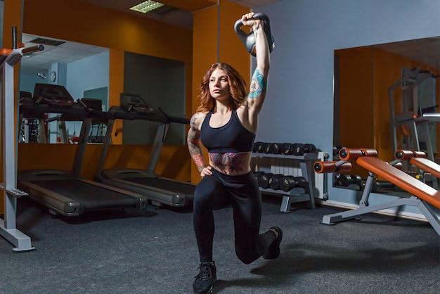 A garota está fazendo exercícios com pesos na posição de corredor do tripé. menina com pesos no ginásio. Foto Premium