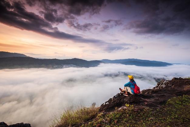 A garota está olhando para o mar de névoa na alta montanha.