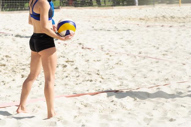A garota está se preparando para servir a bola na quadra de vôlei de praia.