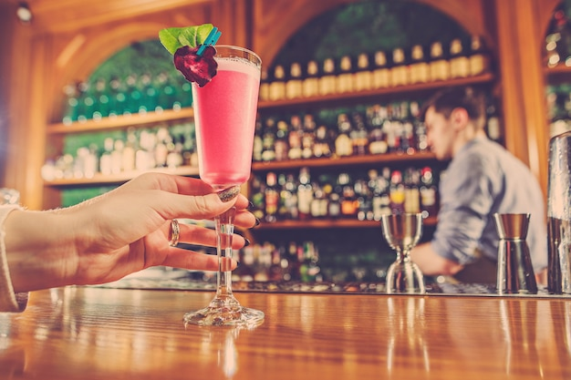 A garota está segurando na mão um copo de bebida alcoólica