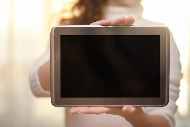 A garota está segurando o tablet. a garota tem um computador com uma tela nas mãos. as mãos seguram a tela com um espaço vazio.