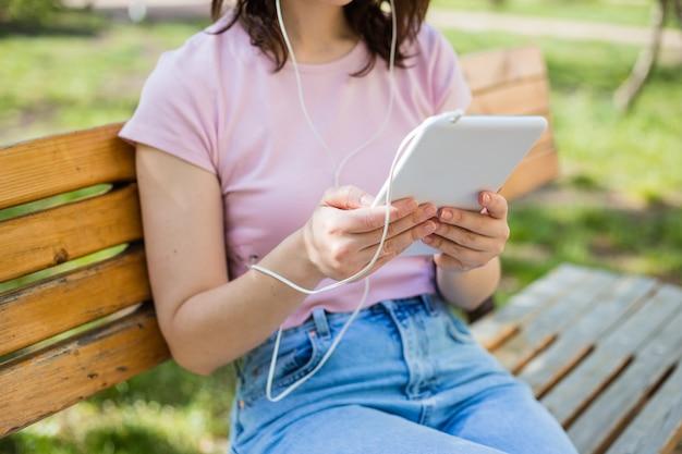 A garota está segurando um tablet. fechar-se. a menina ouve música através de fones de ouvido no tablet.