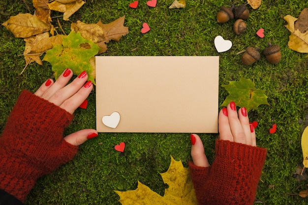 A garota está segurando uma folha de papel vazia vintage no outono park.