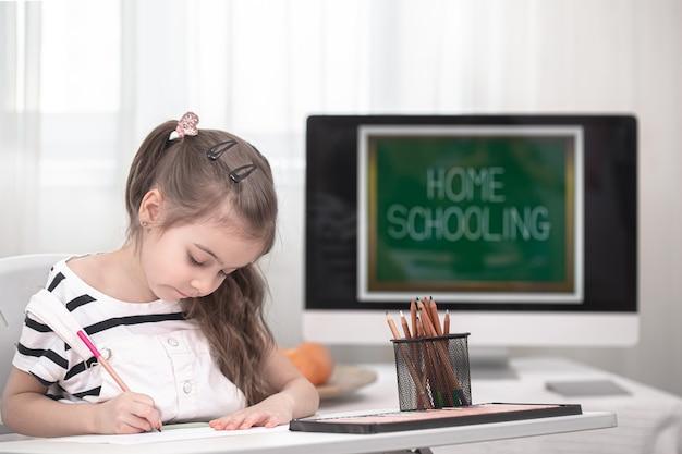 A garota está sentada à mesa e fazendo a lição de casa. a criança aprende em casa. conceito de escolaridade e educação em casa.