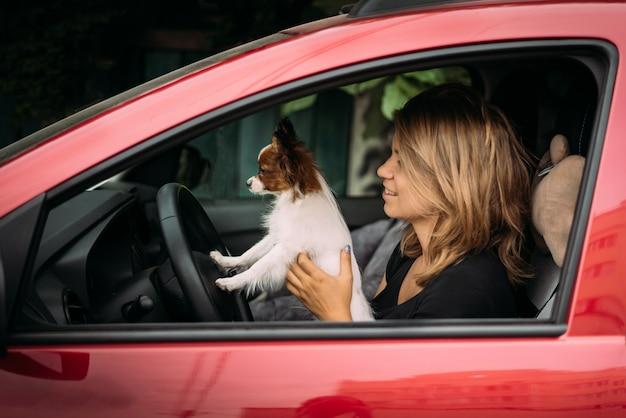 A garota está sentada atrás em um carro vermelho no banco do motorista