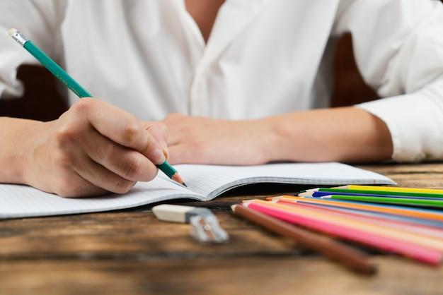 A garota está sentada em uma mesa com muitos materiais escolares.