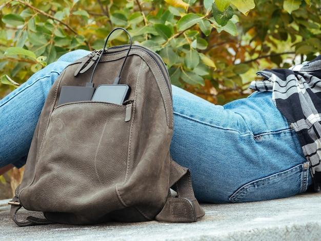 A garota está sentada na natureza e esperando o smartphone carregar do banco de energia