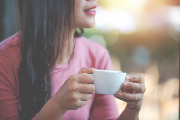 A garota está tomando café com prazer na cafeteria.