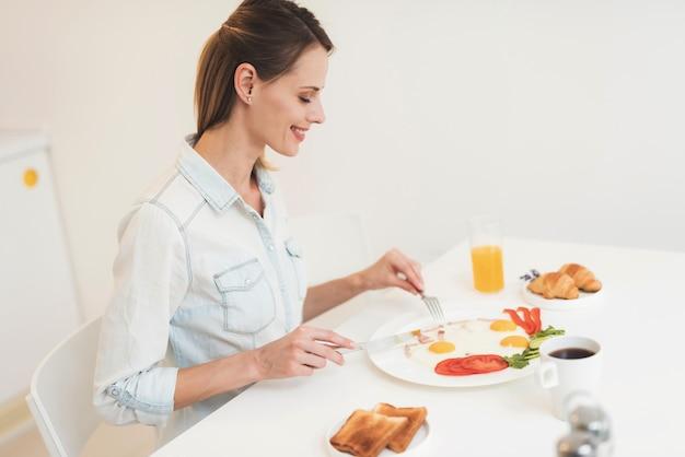 A garota está tomando café da manhã na cozinha
