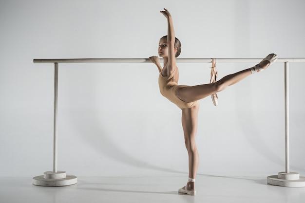 A garota está treinando perto do barril de balé. ela está na aula de balé. ela quer se tornar uma bailarina.