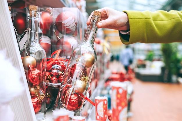 A garota estende a mão para a garrafa no balcão da loja com bolas decorativas,