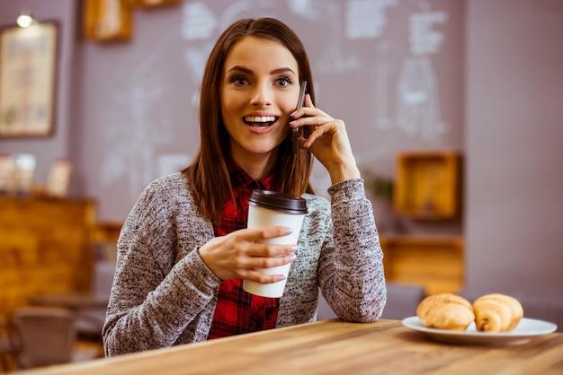 A garota fala por telefone e come.