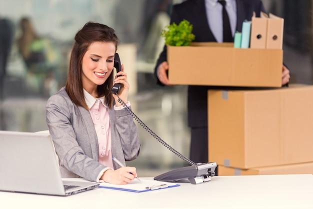 A garota fala por telefone e trabalha no computador.