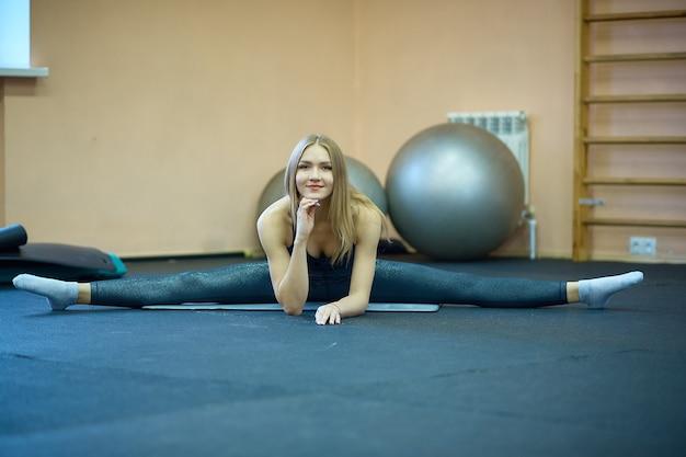 A garota faz alongamento e ioga na academia após o treino e pilates, uma aula em um clube esportivo após a quarentena.