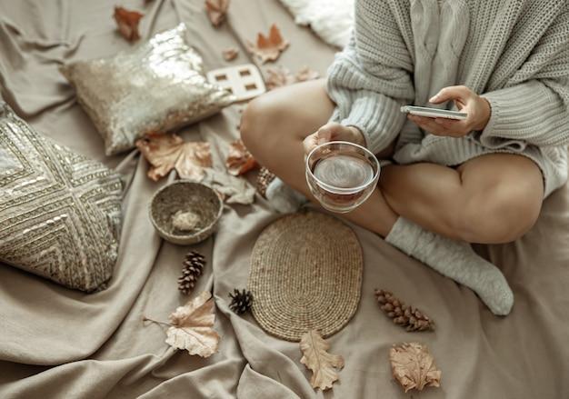 A garota faz uma foto de uma xícara de chá entre as folhas de outono, composição de outono.