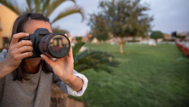 A garota faz uma foto em uma câmera slr profissional ao ar livre na natureza de perto.