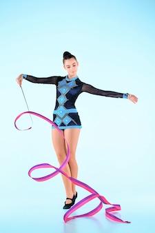 A garota fazendo ginástica dança com fita colorida em um espaço azul