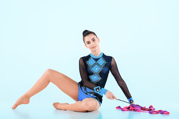 A garota fazendo ginástica dança com fita colorida em uma parede azul