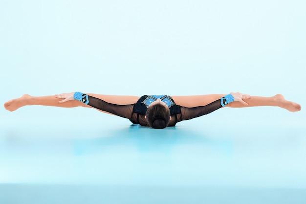 A garota fazendo ginástica dança em um espaço azul