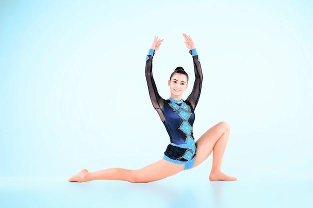 A garota fazendo ginástica dançar em um azul