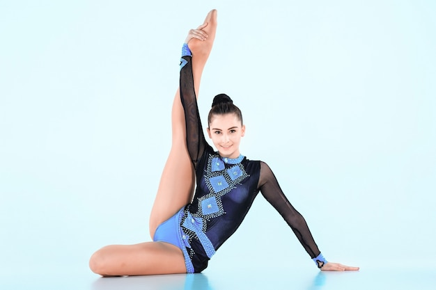 A garota fazendo ginástica dançar em uma parede azul