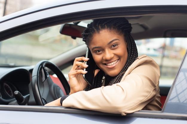 A garota feliz dirigindo um carro com um telefone, afro-americana